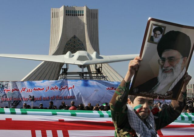 An Iranian boy holds a portrait of supreme leader, Ayatollah Ali khamenei as he walks past a replica of the captured US RQ-170 drone on display next to the Azadi (Freedom) tower during the 33rd anniversary of the Islamic revolution in Tehran on February 11, 2012