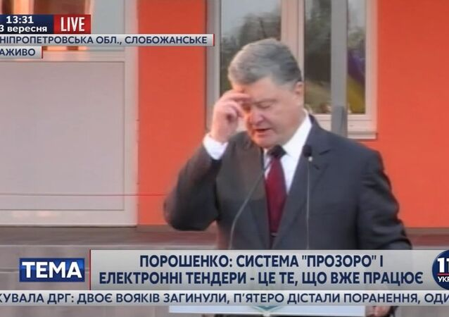 Ukrainian President Petro Poroshenko makes gesture of the sign of the cross as he promises a new $1 billion loan tranche from the IMF.