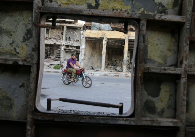 A man rides a motocycle near damaged buildings in the rebel held Old Aleppo, Syria, September 14, 2016