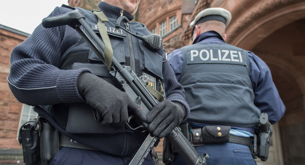 A police officer holds a submachine gun at the main train station in Giessen, central Germany, Friday, March 25, 2016