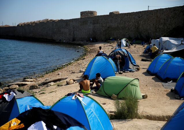 Refugees and migrants sit next to tents set on the beach next to a medieval fortification wall, at the Souda municipality run camp for refugees and migrants, on the island of Chios, Greece, September 7, 2016.