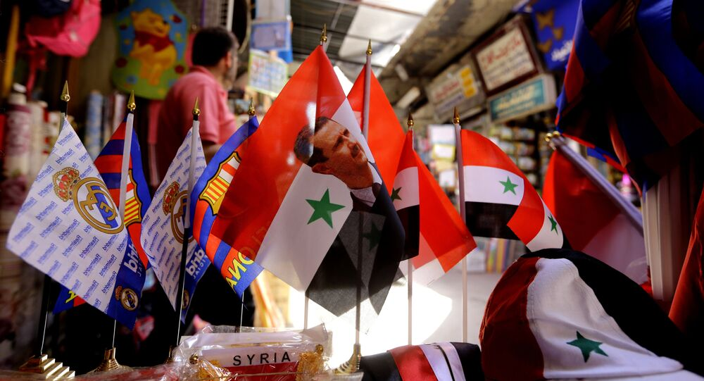 Syrian flags bearing the portrait of President Bashar al-Assad are displayed at the Hamidiyeh popular market in the old part of the capital Damascus on June 13, 2016