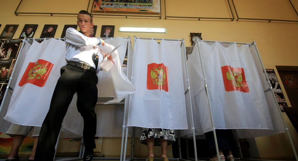 A Russian navy serviceman walks out of a voting booth at a polling station during the Russian parliamentary election in Sevastopol, Crimea, September 18, 2016.