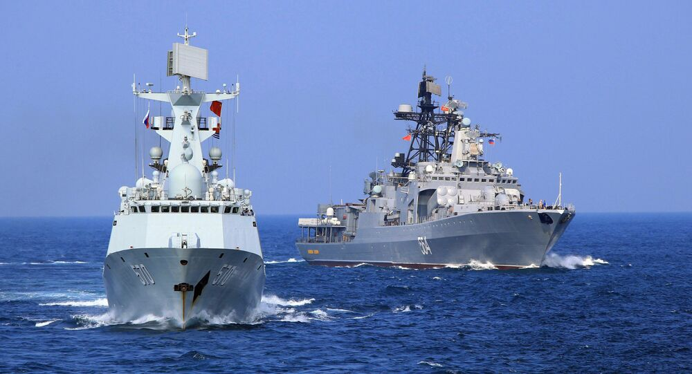 In this Friday, Sept. 16, 2016 photo released by Xinhua News Agency, Chinese Navy frigate Huangshan, left, and Russian Navy antisubmarine ship Admiral Tributs take part in a joint naval drill at sea off south China's Guangdong Province.