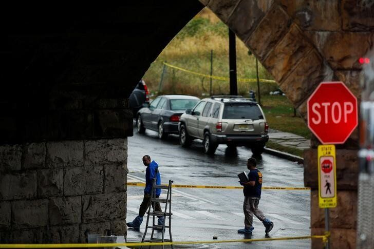 Federal Bureau of Investigation (FBI) officials walk near the area where an explosive device left at a train station was detonated by the authorities in Elizabeth, New Jersey, U.S., September 19, 2016.