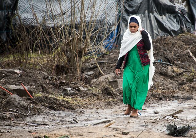 A migrant woman walks along a muddy path in the so-called Jungle refugee and migrant camp in Calais, on February 24, 2016.