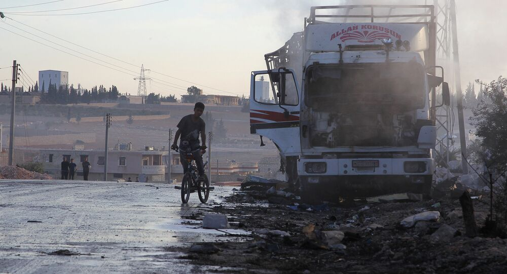 A boy rides a bicycle near a damaged aid truck after an airstrike on the rebel held Urm al-Kubra town, western Aleppo city, Syria September 20, 2016.