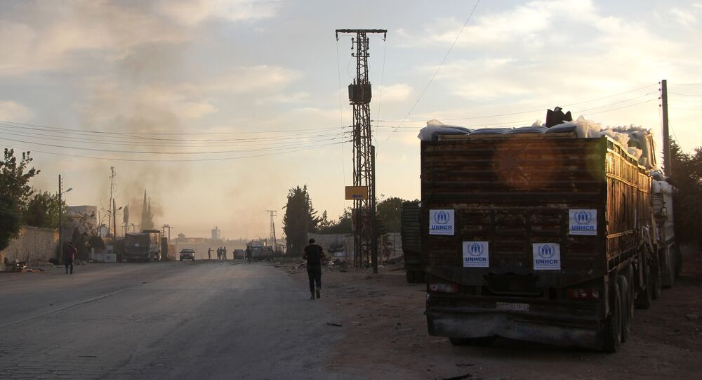 Smoke rises in the distance as Syrians gather near damaged trucks carrying aid on the side of the road in the town of Orum al-Kubra on the western outskirts of the northern Syrian city of Aleppo on September 20, 2016, the morning after a convoy delivering aid was hit by a deadly air strike
