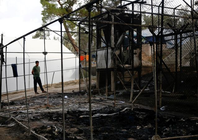 A migrant stands next to a burned tent at the Moria migrant camp, after a fire that ripped through tents and destroyed containers during violence among residents, on the island of Lesbos, Greece, September 20, 2016.