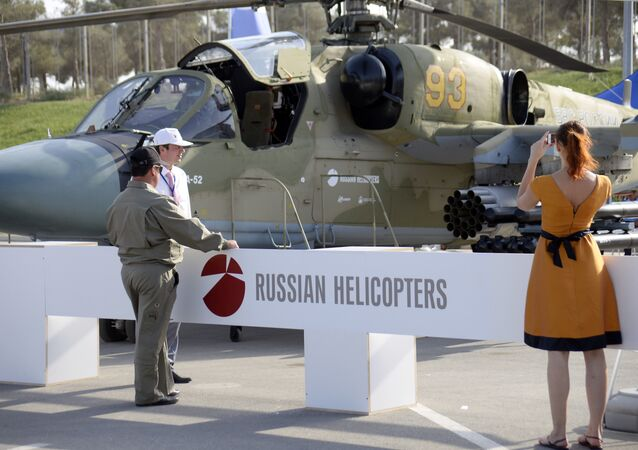 A woman as she takes a photo of a Russian military helicopter KA-52 at the ADEX 2014 International Defence Industry Exhibition in Baku on September 11, 2014