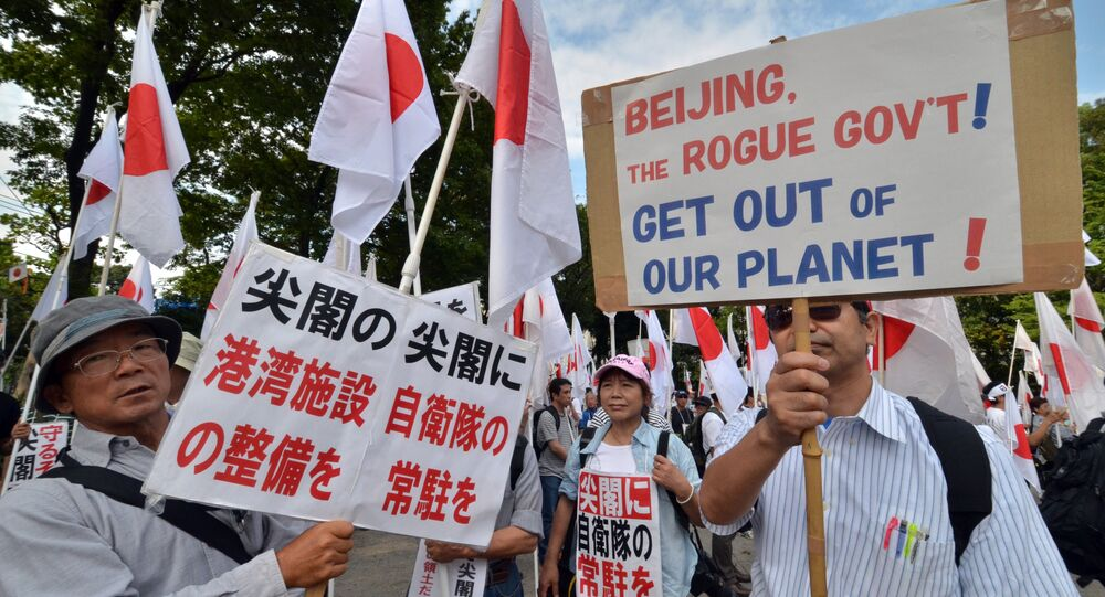 Right wing acrivists hold national flags and placards to protest against China in Tokyo on September 22, 2012