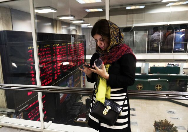 An Iranian woman uses a mobile phone next to a stock market activity board at the stock exchange in the capital Tehran on July 27, 2015
