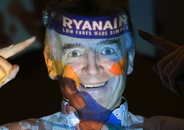 Chief Executive Officer of Irish airline Ryanair Michael O'Leary poses with his company's logo projected on his face as he attends a press conference at a hotel in London on August 31, 2016.