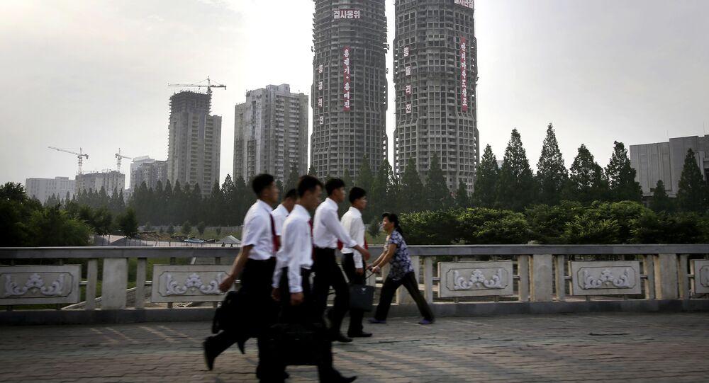 "In this June 27, 2016, photo, North Korean men and women walk past buildings under construction on ""Ryomyong Street,"" in Pyongyang, North Korea"