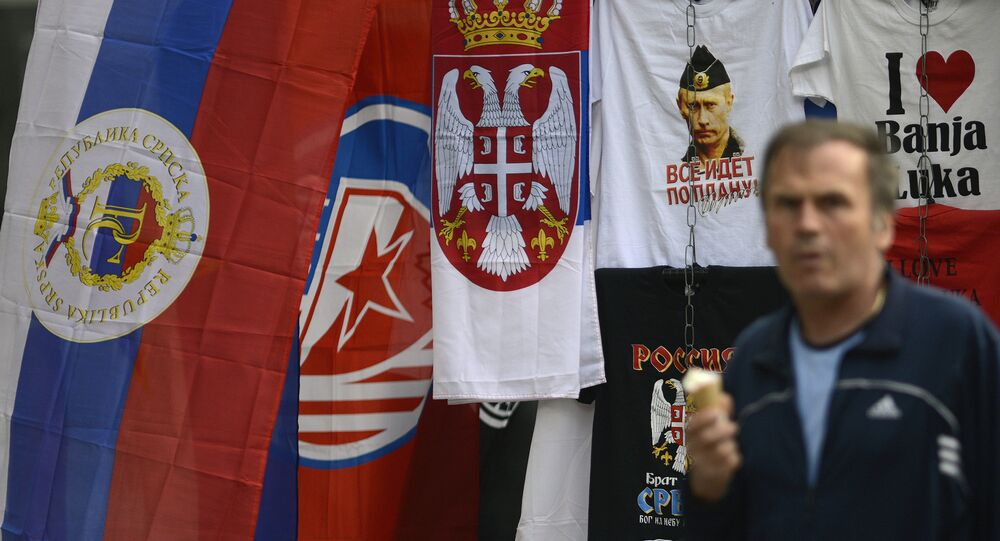 In this photo taken on Wednesday, Sept. 21, 2016. Bosnian man passes by flags of Bosnia's Serb mini state Republic of Srpska and t-shirt with photos of Russian President Vladimir Putin in the Bosnian town of Banja Luka, 240 kms (150 miles) northwest of the Bosnian capital of Sarajevo