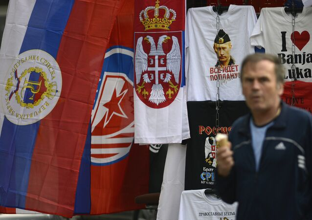 In this photo taken on Wednesday, Sept. 21, 2016. Bosnian man passes by flags of Bosnia's Serb mini state Republic of Srpska and t-shirt with photos of Russian President Vladimir Putin in the Bosnian town of Banja Luka, 240 kms (150 miles) northwest of the Bosnian capital Sarajevo