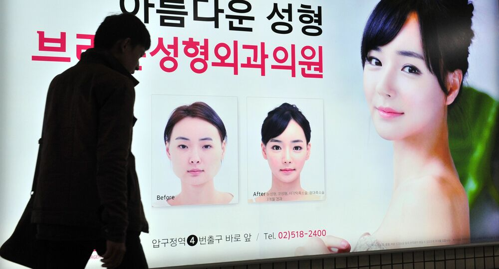 A pedestrian walks past an advertisement for plastic surgery clinic at a subway station in Seoul on March 26, 2014