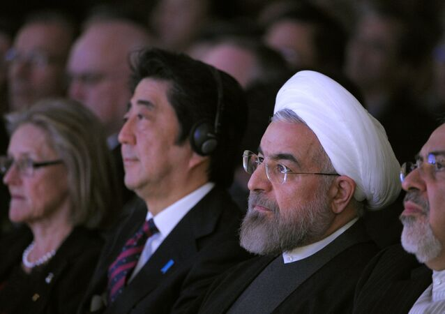 Iranian President Hassan Rouhani (R) sits next to Japanese Prime Minister Shinzo Abe (L) during the opening session of the World Economic Forum in Davos on January 22, 2014