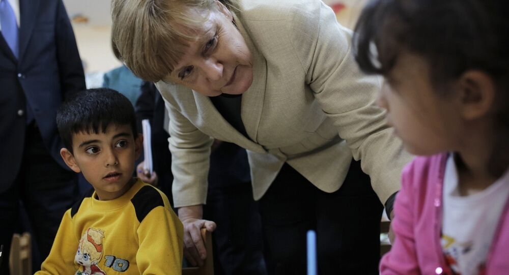 German Chancellor Angela Merkel talks with refugee children at a preschool, during a visit to a refugee camp on April 23, 2016 on the Turkish-Syrian border in Gaziantep
