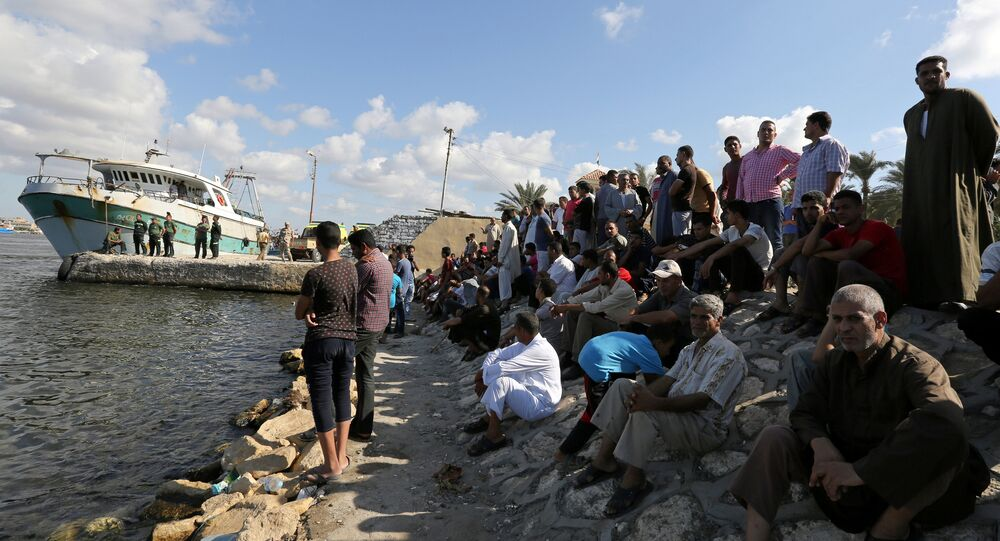 People gather along the shore of the Mediterranean Sea during a search for victims after a migrant boat capsized, in Al-Beheira, Egypt, September 22, 2016