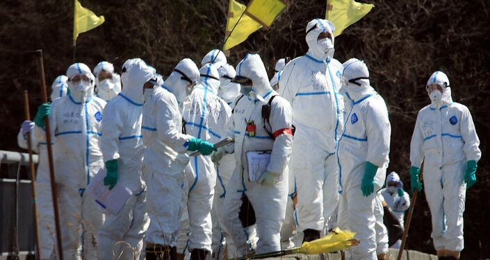 Policemen in radiation proof suits gather to search for missing victims in Namie, Fukushima prefecture.
