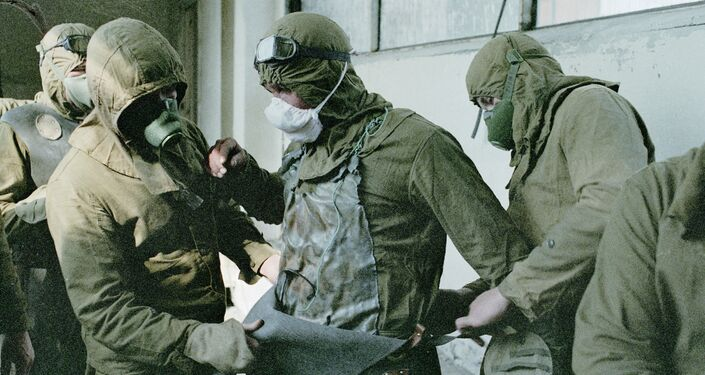 Personnel assigned to remove debris from the roof of the damaged Chernobyl Nuclear Plant unit don protective suits.