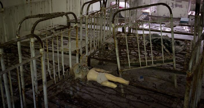 A doll with a gas mask lies on the frame of a bed in the sleeping room of a kindergarten in the deserted town of in Pripyat.