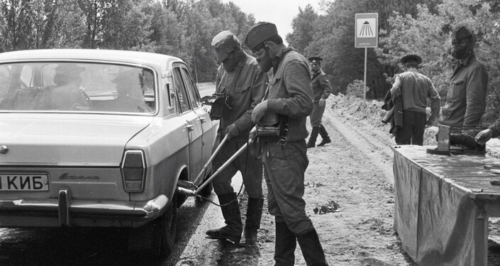 Soldiers check radiation levels of cars leaving the city of Chernobyl.