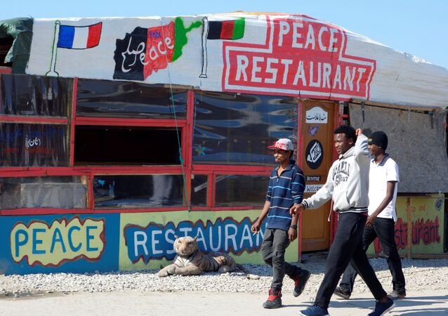 Migrants pass by the Peace Restaurant in the northern area of the camp called the Jungle in Calais, France, September 7, 2016