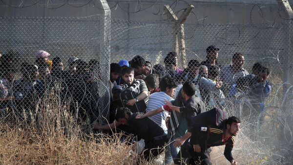 File photo taken from the Turkish side of the border between Turkey and Syria, in Akcakale, Sanliurfa province, southeastern Turkey, Syrian refugees burst into Turkey after breaking the border fence and crossing from Syria cross into Turkey - Sputnik International