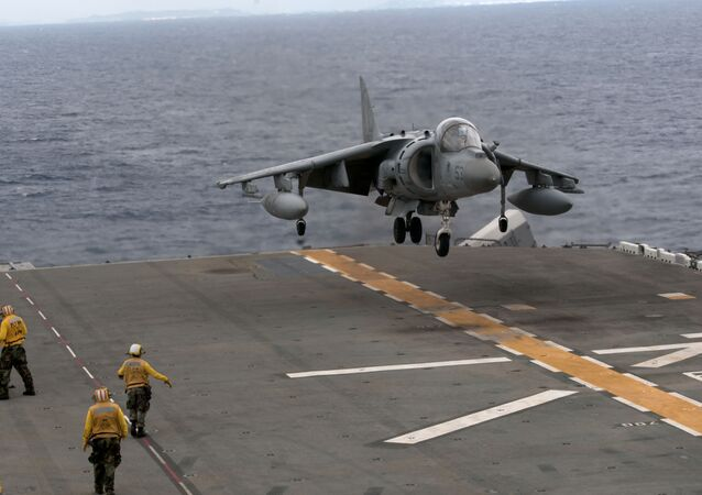 An AV-8B Harrier with Marine Attack Squadron 214 lands on the flight deck of the forward-deployed amphibious assault ship USS Essex (LHD 2)