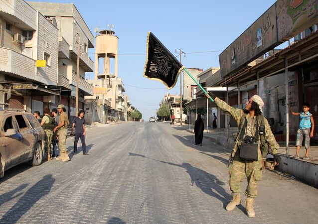 A terrorist from the Jund al-Aqsa group raises an Islamist flag after taking control of the northern Syrian town of Tayyibat al-Imam, northwest of Hama from Syrian government forces on August 31, 2016