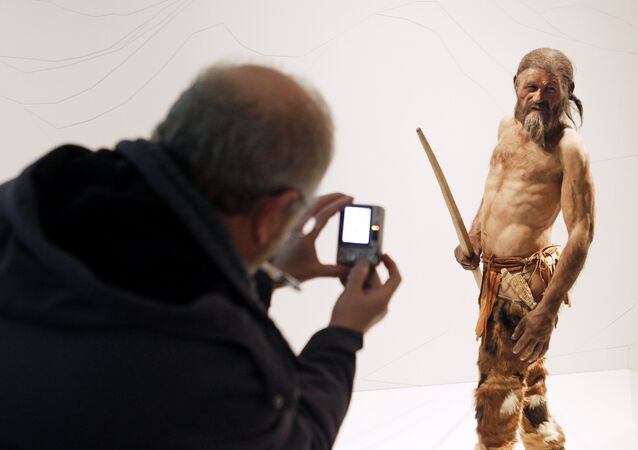 A man takes pictures of a statue representing an iceman named Oetzi, discovered on 1991 in the Italian Schnal Valley glacier, is displayed at the Archaeological Museum of Bolzano on February 28, 2011 during an official presentation of the reconstrution