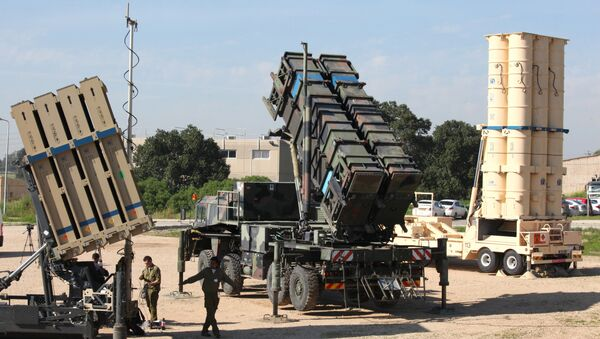 Israeli soldiers walk near an Israeli Irone Dome defence system (L), a surface-to-air missile (SAM) system, the MIM-104 Patriot (C), and an anti-ballistic missile the Arrow 3 (R) during Juniper Cobra's joint exercise press briefing at Hatzor Israeli Air Force Base in central Israel, on February 25, 2016. Juniper Cobra, is held every two years where Israel and the United States train their militaries together to prepare against possible ballistic missile attacks, as well as allowing the armies to learn to better work together. - Sputnik International