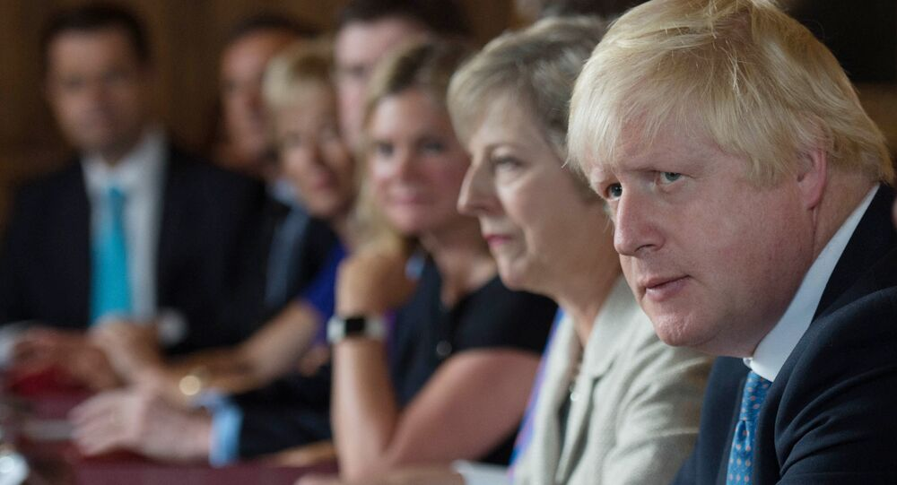 British Foreign Secretary Boris Johnson (2R) sits next to British Prime Minister Theresa May (3R) during a meeting of the cabinet at the Prime Minister's country retreat Chequers near the village of Ellesborough in Buckinghamshire, northwest of London, on August 31, 2016.