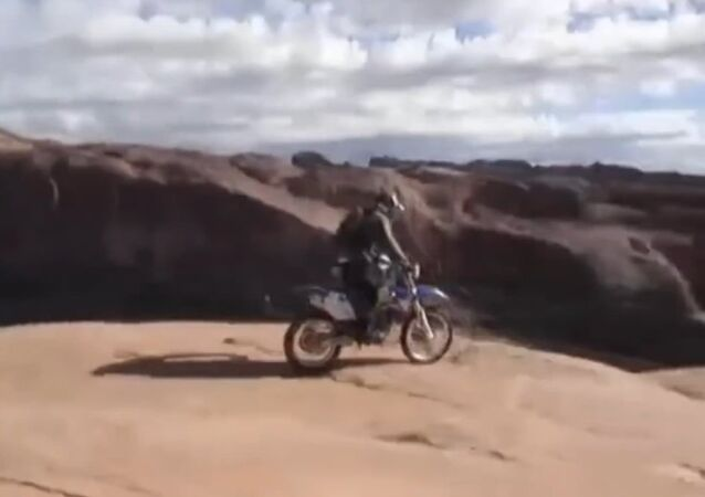 Crazy biker rides around cliff