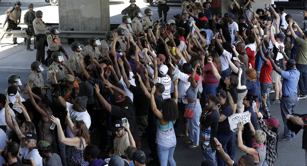 Police form a line in front of protesters, Wednesday, Sept. 28, 2016, in El Cajon, Calif. Dozens of demonstrators on Wednesday protested the killing of a black man shot by an officer after authorities said the man pulled an object from a pocket, pointed it and assumed a shooting stance.