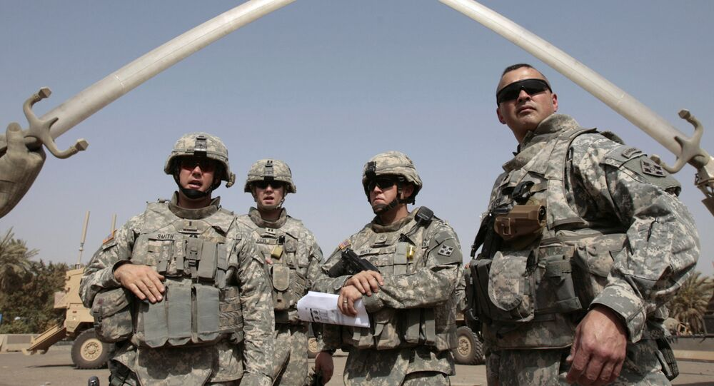 US soldiers stand near the landmark Hands of Victory, built by executed Iraqi president Saddam Hussein to commemorate Iraq's victory in the Iran-Iraq war, inside Baghdad's Green Zone as they prepare to go on a mission on July 5, 2008