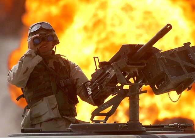 A US soldier looks through a pair of binoculars as a fire in the Rumeila oil field burns in the background in southern of Iraq, Sunday, March 30, 2003.