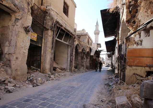 Syrian government soldiers walk in the damaged al-Farafira souk in the government-held side of Aleppo's historic city centre on September 16, 2016