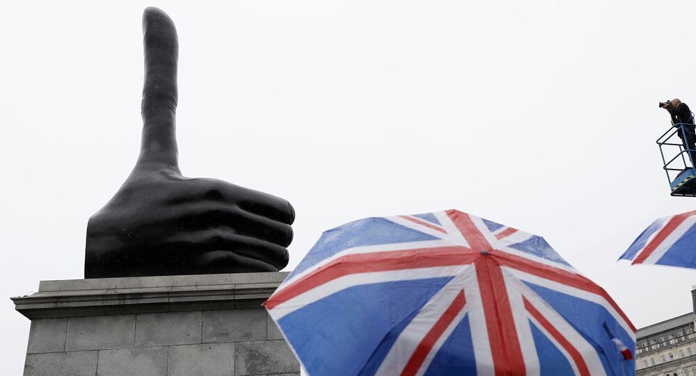 A tourist with union jack umbrella looks at the artwork Really Good by David Shrigley on the fourth plinth at Trafalgar Square in central London, Britain September 29, 2016.