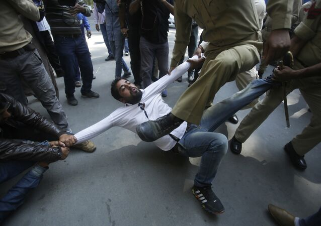 Indian policemen try to detain a supporter of Jammu and Kashmir state lawmaker, Engineer Abdul Rashid Sheikh, during a protest in Srinagar, Indian controlled Kashmir, Monday, Sept. 26, 2016