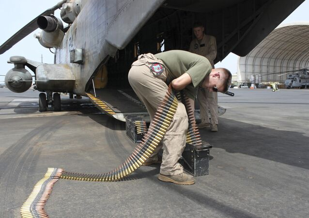 In this photo taken May 26, 2010, Sgt. Tyler Johnson, 23, of Portland, Ore., loads ammunition cans for a .50 caliber machine gun mounted on the back of a Marine CH53 at Camp Lemonnier, Djibouti, the only U.S. base in Africa