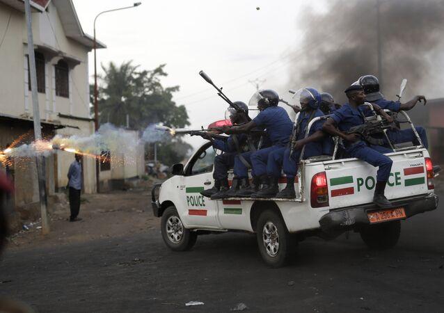Burundi riot police fire tear gas as they chase demonstrators during clashes in Bujumbura, Burundi, Wednesday April 29, 2015