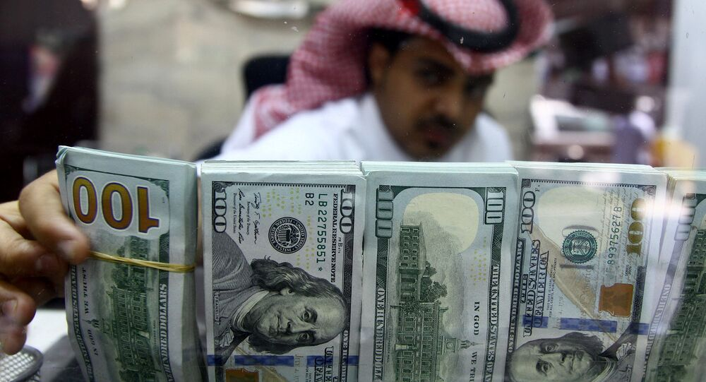 A Saudi money changer, pictured through a glass, arranges U.S banknotes at a currency exchange shop in Riyadh, Saudi Arabia September 29, 2016