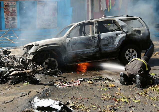 A firefighter tries to extinguish fire from the wreckage of a burning vehicle following an attack on a restaurant by the Somali Islamist group al Shabaab in the capital Mogadishu, Somalia, October 1, 2016