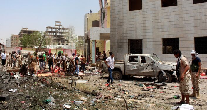Fighters loyal to the government gather at the site of a suicide car bombing in Yemen's southern city of Aden, Yemen, Monday, Aug. 29, 2016