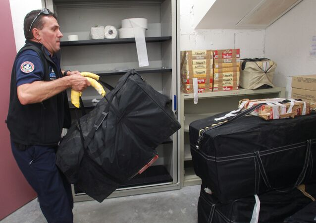 A custom officer of Ax-les-Thermes carries a bag of cigarettes seized during an operation monitoring the smuggling of cigarettes from the Principality of Andorra in the Pyrenees mountains on July 17, 2013