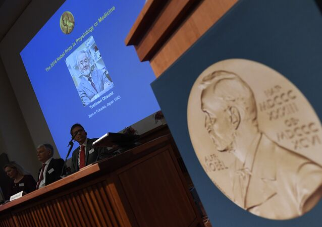 A portrait of the 2016 Nobel Medicine Prize winner Yoshinori Ohsumi of Japan is displayed behind members of the Nobel Committtee for Physiology or Medicine 2016 during a press conference to announce the winner of the 2016 Nobel Prize in Medicine at the Nobel Forum in Stockholm on October 3, 2016.