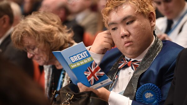 A delegate reads a leaflet entitled BREXIT, how do we do it? as he sits in the audience on the second day of the annual Conservative Party conference at the International Convention Centre in Birmingham, central England, on October 3, 2016. - Sputnik International